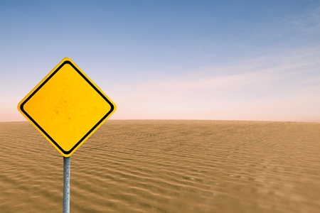 composite image: Composite image of a sign in the desert with a blue sky