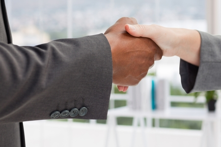 composite image: Composite image of handshake in an office