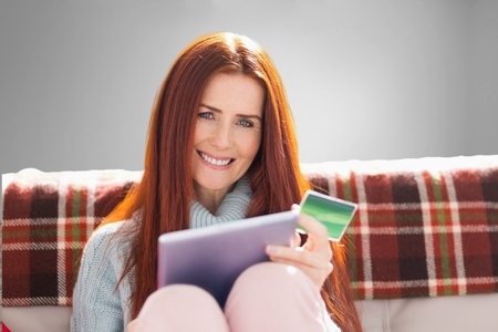 composite image: Composite image of woman is doing shopping online at home Stock Photo