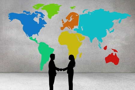 composite image: Composite image of businesspeople are handshaking in front of a world map drawing on a wall