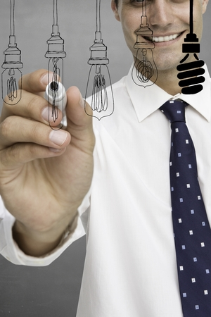 composite image: Composite image of businessman is drawing light bulb on a screen