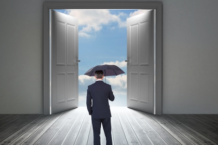composite image: Composite image of businessman is holding an umbrella in front of a door