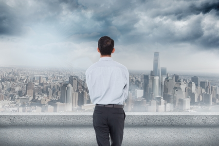 composite image: Composite image of businessman is looking the cityscape on a cloudy day