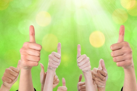 composite image: Composite image of thumbs up against a green background
