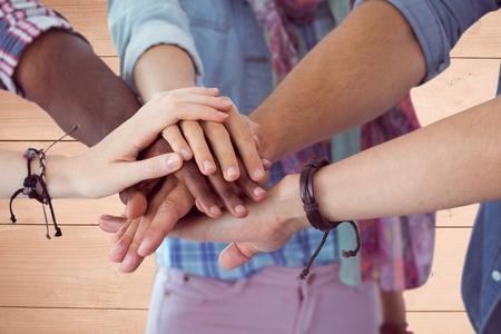 trato amable: Imagen compuesta de amigos est� uniendo sus manos juntas sobre un fondo de madera