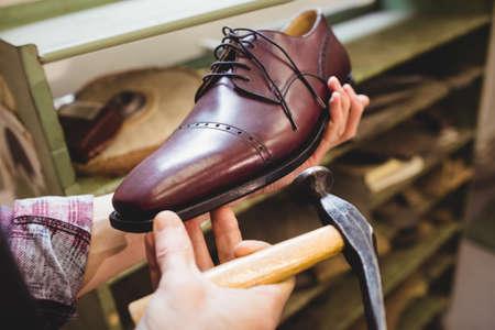 cobbler: Close up of cobbler making a shoe with a hammer LANG_EVOIMAGES