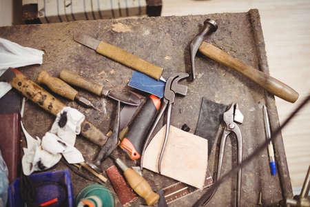 cobbler: Tools of cobbler on a table in a workshop LANG_EVOIMAGES