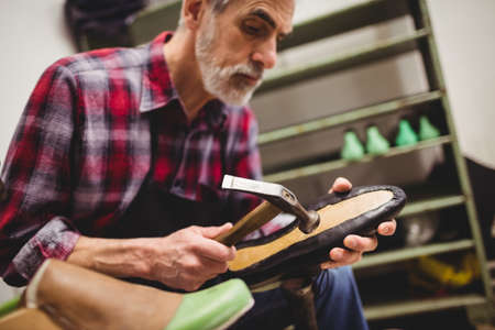 hammering: Cobbler hammering on the sole of a shoe in his workshop