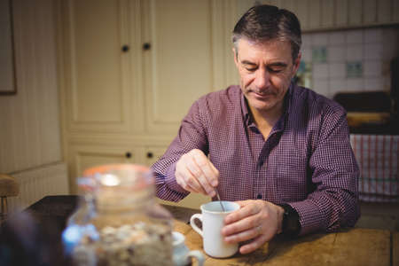 weekend activity: Mature man is mixing his drink in his kitchen