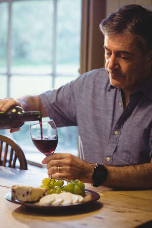 classy house: Portrait of mature man filling a glass of wine in his country house