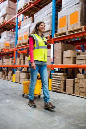 superintendent: Happy woman pushing warehouse floor in a warehouse