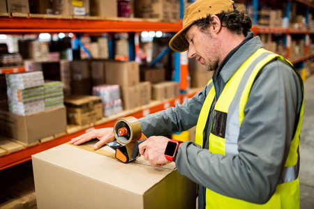 taping: Side view of man worker taping up a box in a warehouse