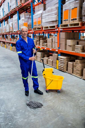 superintendent: Smiling man moping warehouse floor in a warehouse LANG_EVOIMAGES