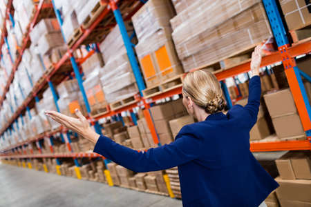 depot: Side view of warehouse manager raising her arms in a depot