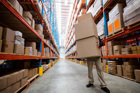 carrying: Worker carrying boxes in warehouse LANG_EVOIMAGES