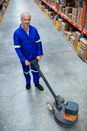 superintendent: Man cleaning warehouse floor with machine in a warehouse LANG_EVOIMAGES