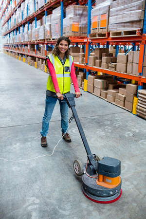 superintendent: Woman cleaning warehouse floor with machine in a warehouse LANG_EVOIMAGES