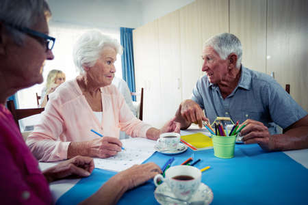sheltered accommodation: Group of seniors drawing and interacting in the retirement house