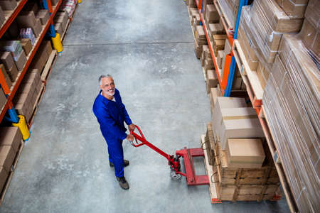 pallet truck: High angle view of man worker smiling with the pallet truck in a warehouse