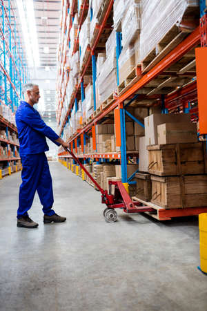 pallet truck: Man worker using pallet truck in the warehouse