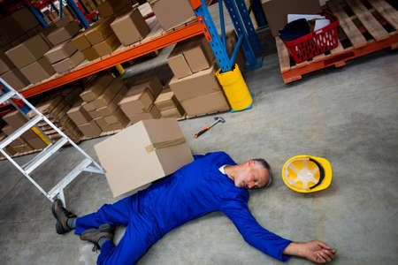 fainted: High angle view of unconscious worker lying on the floor in the warehouse LANG_EVOIMAGES