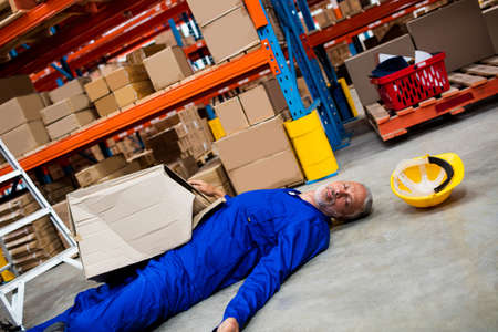 the unconscious: Unconscious worker lying on the floor in the warehouse