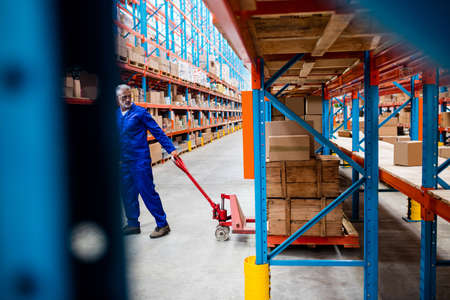pallet truck: Man worker pulling the pallet truck in the warehouse