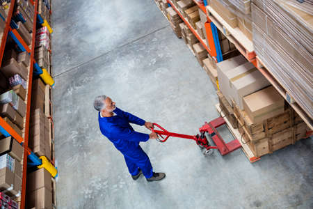 pallet truck: High angle view of man worker pulling the pallet truck in the warehouse