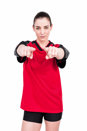 elbow pad: Female athlete posing with elbow pad and pointing the camera on white background Stock Photo