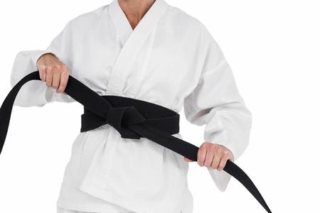 tightening: Female athlete tightening her judo belt on white background Stock Photo