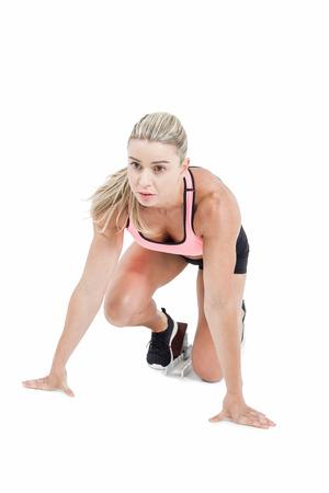 start line: Female athlete on the start line on white background