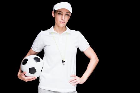 arbitrator: Female athlete holding a soccer ball on black background