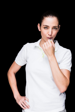 arbitrator: Female athlete blowing a whistle on black background