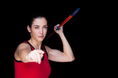 javelin: Female athlete throwing a javelin on black background Stock Photo