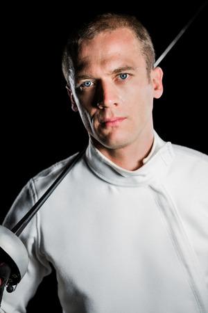 fencing sword: Portrait of swordsman holding fencing sword on black background
