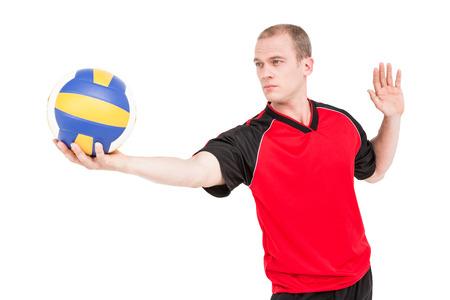 pelota de voley: Deportista que consigue listo para servir mientras juega voleibol en el fondo blanco Foto de archivo