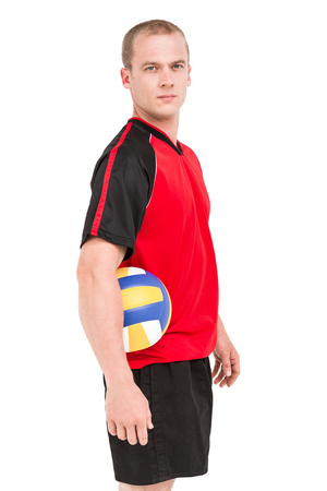 cut the competition: Portrait of sportsman holding a volleyball on white background