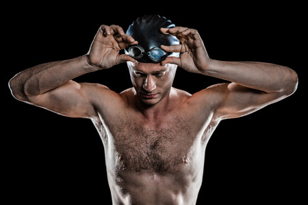 Swimmer looking down and holding swimming goggles on black background