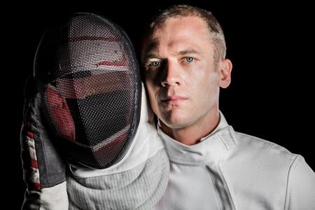 swordsman: Portrait of swordsman holding fencing mask on black background Stock Photo