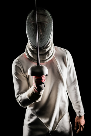 fencing sword: Portrait of man wearing fencing suit practicing with sword on black background Stock Photo