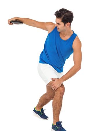 lanzamiento de disco: Decidido atleta masculino jugando lanzamiento de disco en el fondo blanco