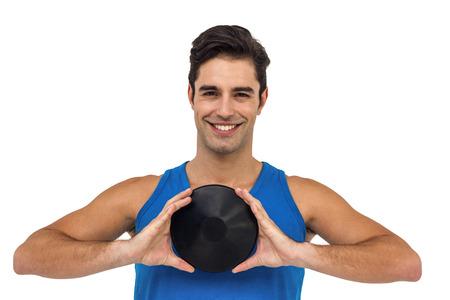 lanzamiento de disco: atleta masculino feliz que presenta con el lanzamiento de disco en el fondo blanco