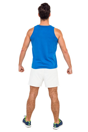 athleticism: Rear view of male athlete standing on isolated white background