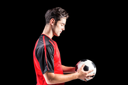 football play: Confident male athlete holding football on black background