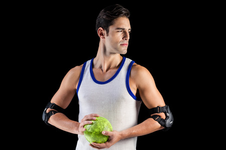 cut the competition: Confident athlete man holding a ball on black background