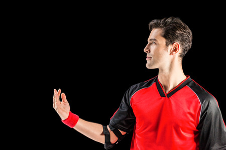 elbow band: Confident athlete man posing on isolated black background Stock Photo