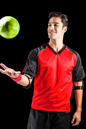 elbow band: Confident athlete man playing with a ball on black background