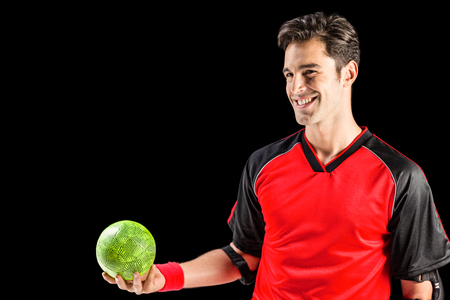 elbow band: Happy athlete man holding a ball on black background