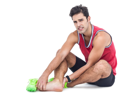 Portrait of male athlete with foot pain on isolated white background Reklamní fotografie