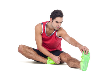 hamstring: Male athlete stretching his hamstring on white background
